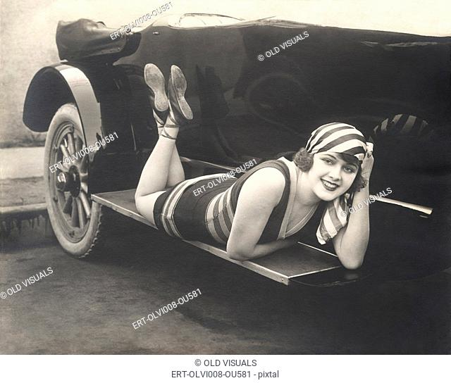Bathing beauty posing on running board of convertible