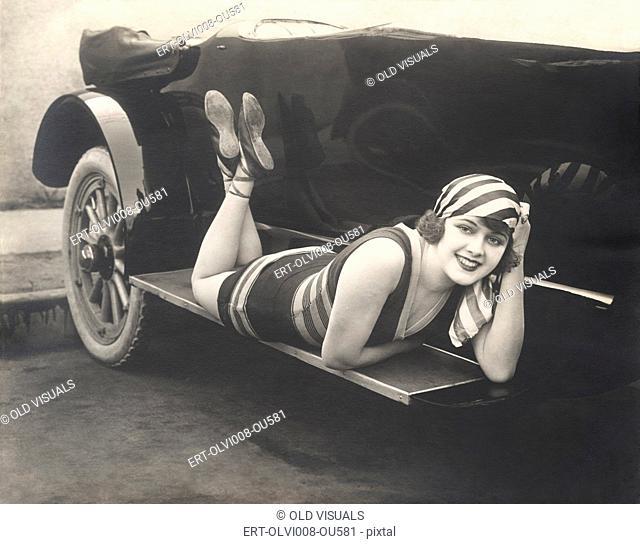 Bathing beauty posing on running board of convertible