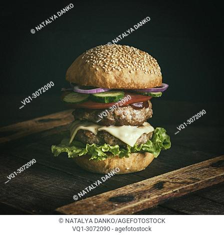 cheeseburger in a bun with sesame seeds, in the middle fresh vegetables and meat cutlets