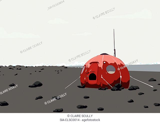 Round red tent in grey barren landscape, snowcapped mountains in distance