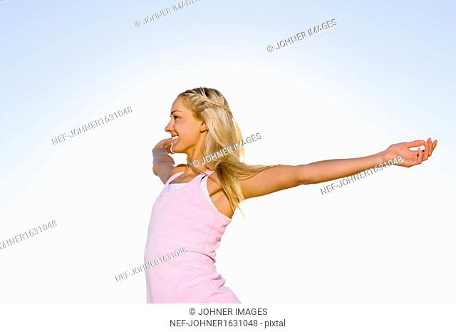 Smiling young woman with outstretched arms
