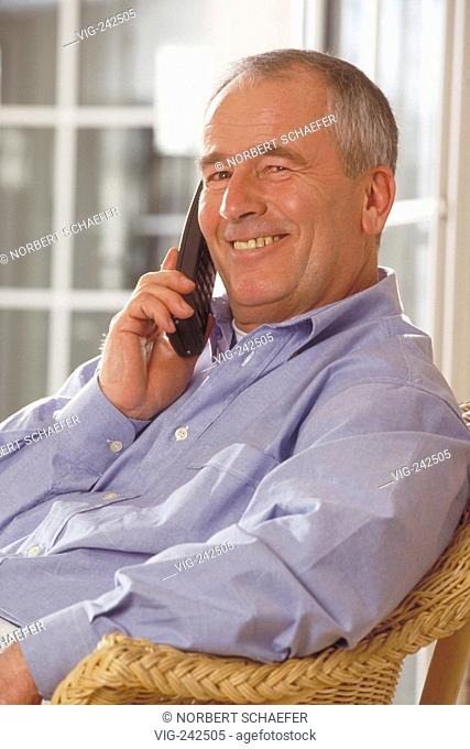 portrait, indoor, ca. 65-year-old senior wearing a lightblue shirt sits laughing on a cane chair in front of a glassdoor making a call with a mobile phone  -...