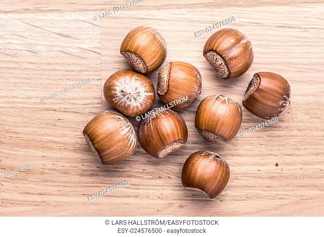 Hazelnuts lying on wood table. Food still life with raw nuts