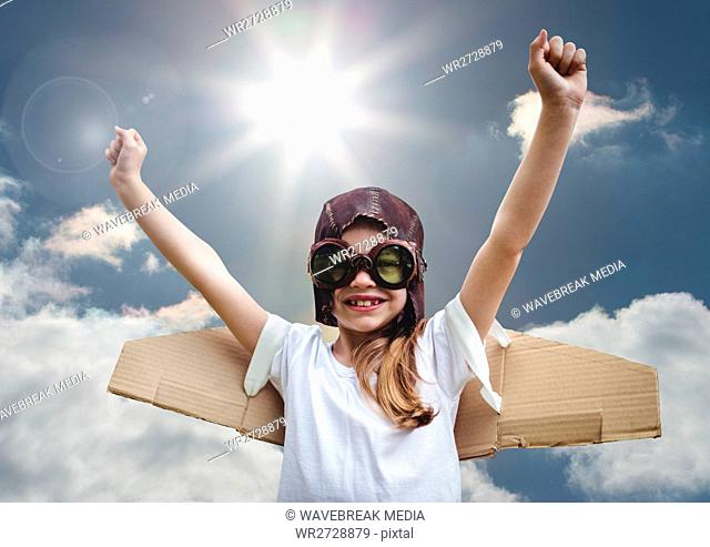 Portrait of excited smiling kid pretending to be a pilot against bright sunlight background