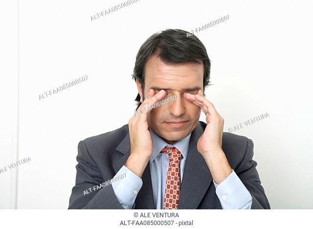 Businessman rubbing eyes