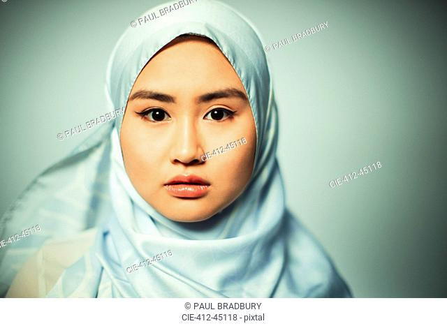 Portrait confident, serious young woman wearing blue silk hijab