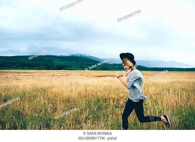 Woman running in wheat field, Edmonton, Canada
