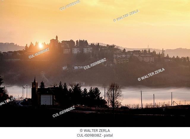 Silhouetted landscape with valley mist at sunset, Langhe, Piedmont. Italy