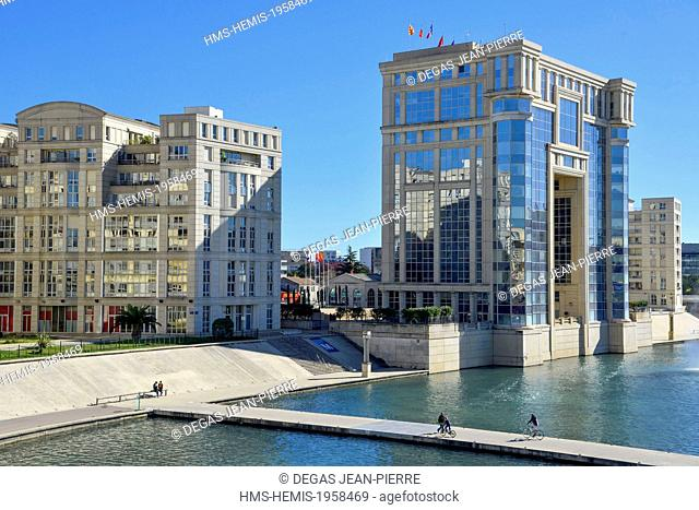 France, Herault, Montpellier, Port Marianne district, Athena footbridge, cyclists crossing the river Le Lez with the Hotel of Region in the background conceived...