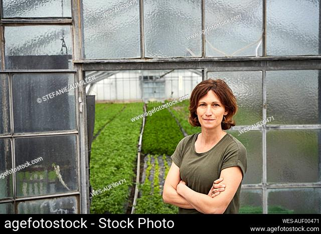 Woman standing in front of greenhouse wuth arms crossed