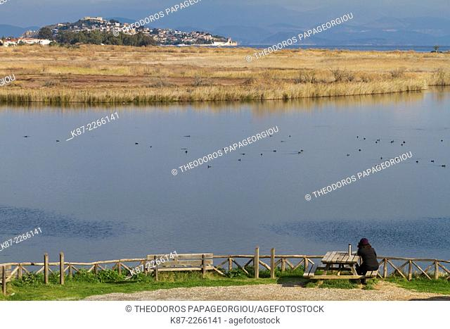 A woman is sitting at Moustos wetland (Natura 2000) and gazing the view towards Astros village. Arcadia, Greece