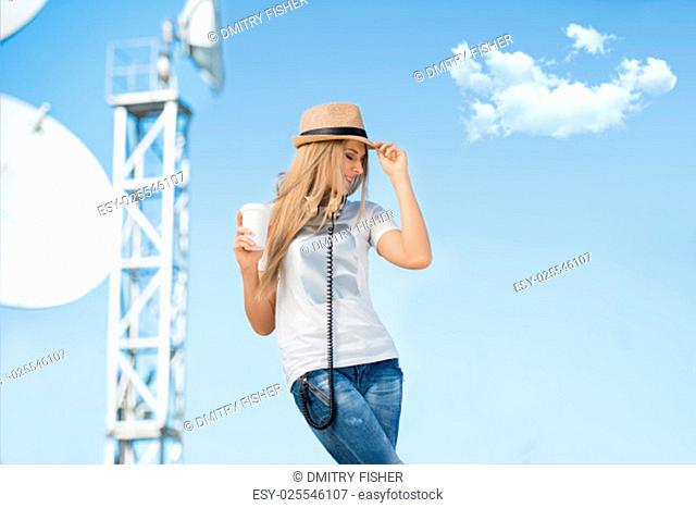 Happy young woman in hat wearing vintage music headphones around her neck, drinking takeaway coffee and posing against background of parabolic satellite dish...