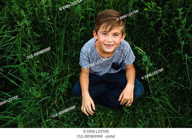Boy looking up at camera on green grassy field