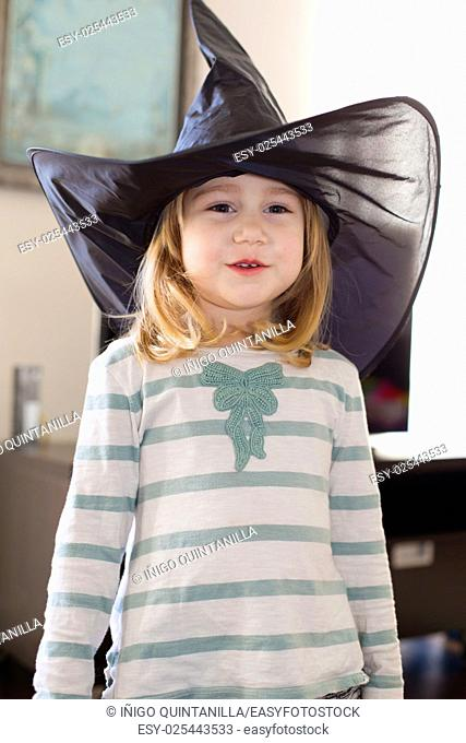 portrait of three years old blonde child with white and green shirt with black big witch hat, looking and smiling, indoor