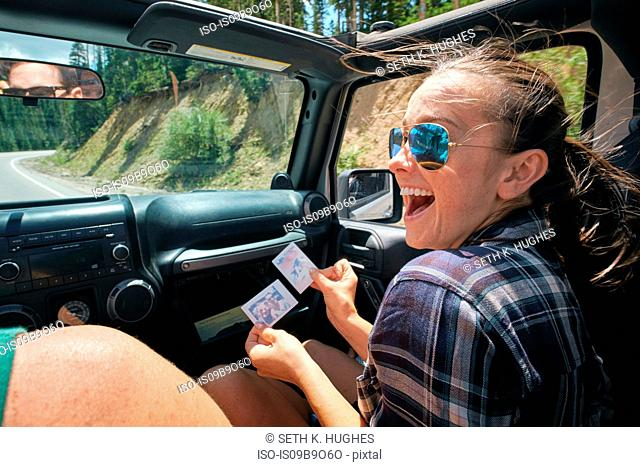 Young woman on road trip with boyfriend laughing at instant photograph, Breckenridge, Colorado, USA