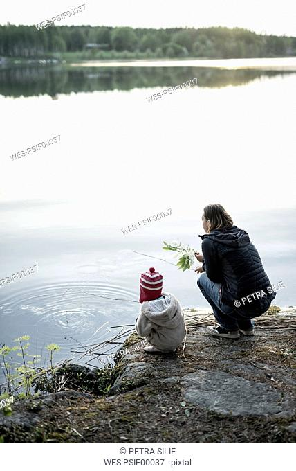 Finland, Kuopio, mother and daughter crouching at a lake