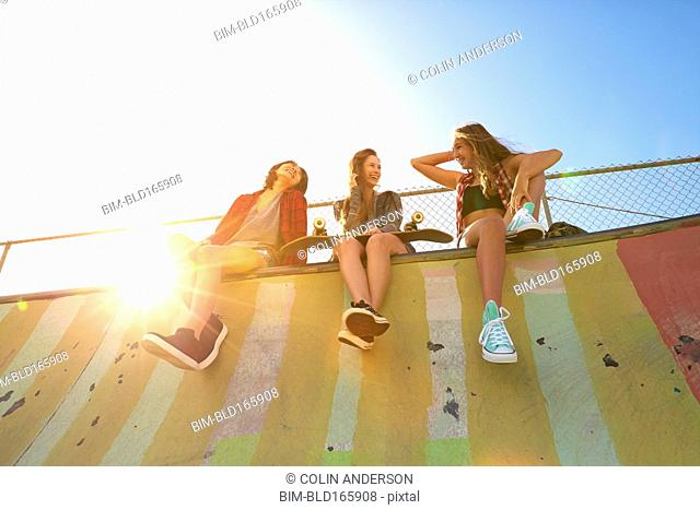 Low angle view of women sitting on ramp at skate park