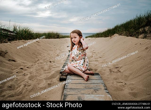 young girl sitting on private board walk going out to lake