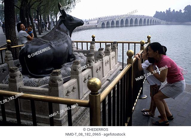 Mother and her daughter looking at the sculpture of a cow, Beijing, China