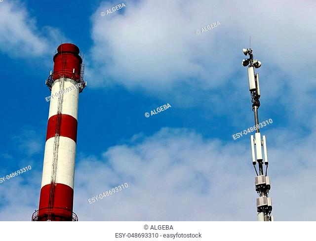 Boiler pipe with red and white stripes and loudspeaker warning system against on a blue sky with clouds. Copy space for text