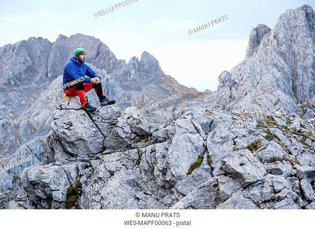 Spain, Picos de Europa, mountaineer resting on rock