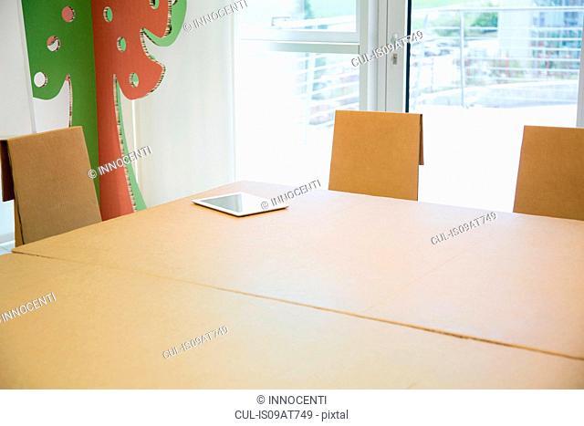 Digital tablet on empty boardroom table
