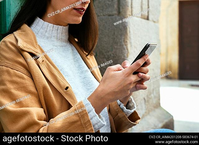 Close up of woman texting a message outdoors