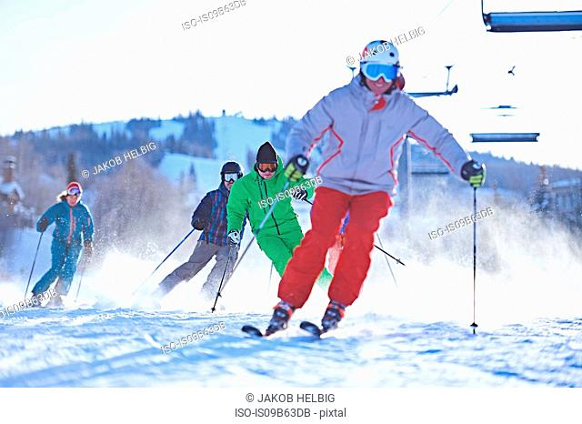Male and female skiers skiing on snow covered ski slope, Aspen, Colorado, USA