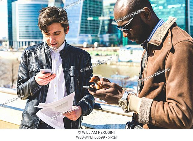 Russia, Moscow, two businessmen using smartphones in the city