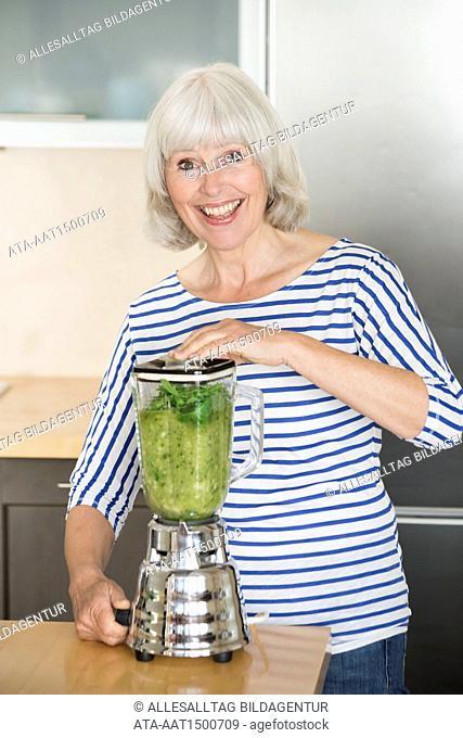 Elderly woman preparing a green smoothie