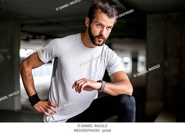 Athlete in parking garage with smartwatch