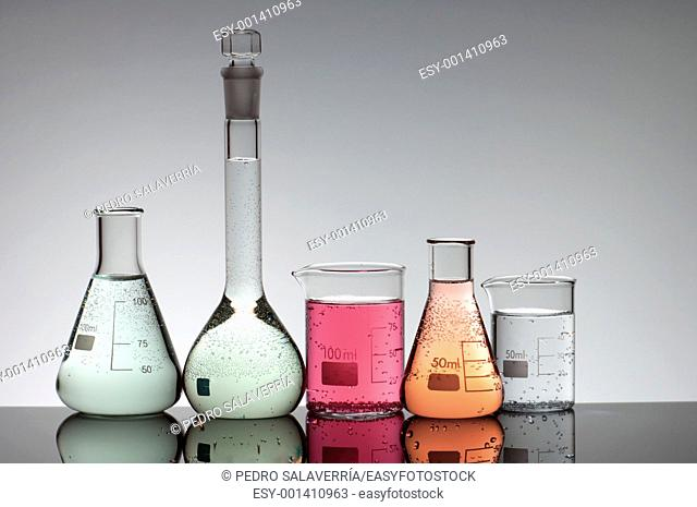 group of five beakers with liquid multi with a white background