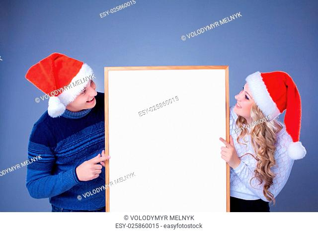 Christmas couple holding white board with empty copy space over blue background. Concept of advertise new year season shopping sale