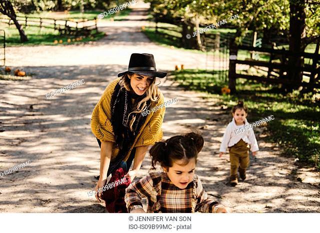 Mother and children on farmland, riding bicycle, Oshawa, Canada, North America