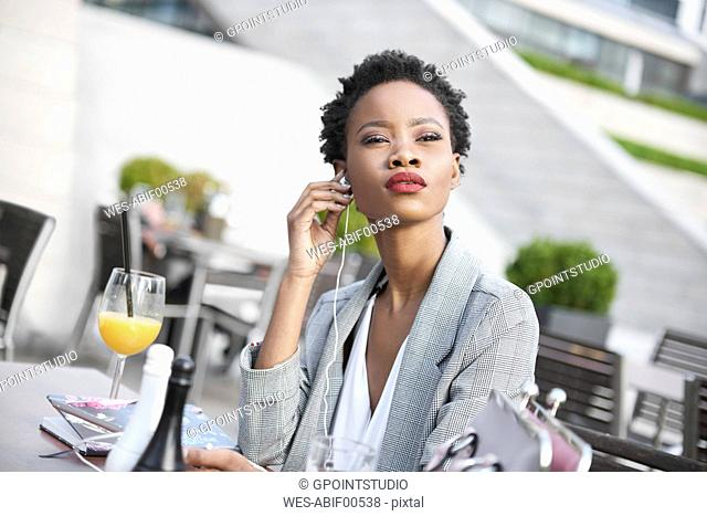Portrait of businesswoman using earphones outdoors