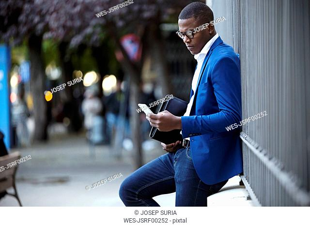 Young businessman wearing blue suit jacket and using smartphone