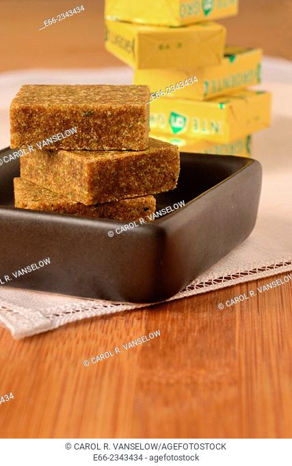 Bouillon blocks stacked in a small black dish. Lower point of view with stack of bouillon cubes in foil wrappers in the background