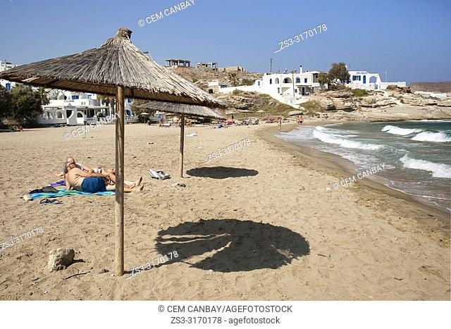 Scene from the beach with thatched umbrallas in the foreground in Naoussa village, Paros Island, Cyclades Islands, Greek Islands, Greece, Europe