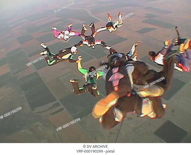 Eleven skydivers free fall in formation and disperse