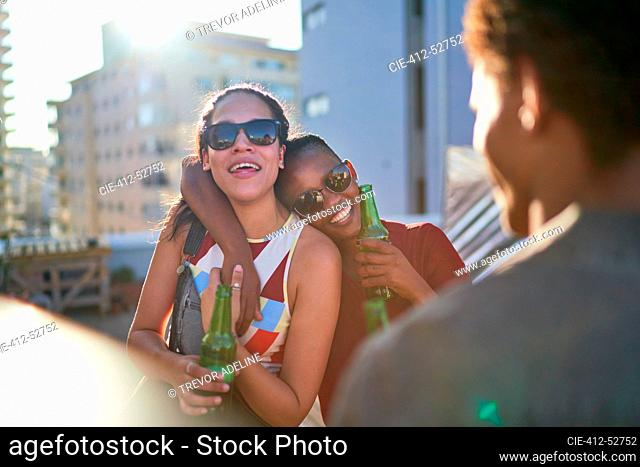 Happy young women friends drinking beer on sunny summer rooftop