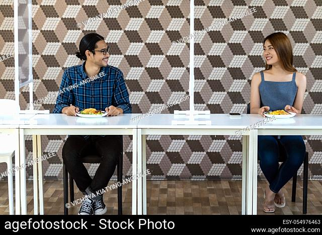 Asian young couple eating out together at new normal social distance restaurant with table shield partition reduce infection of coronavirus covid-19 pandemic