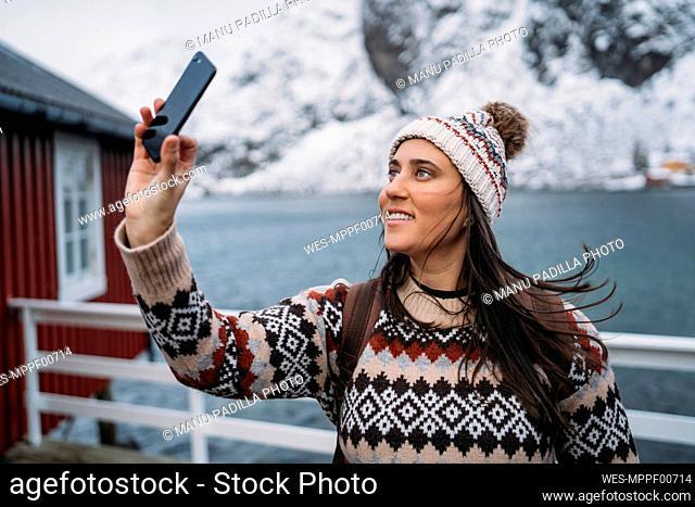 Tourist taking a selfie at the coast, Lofoten, Norway