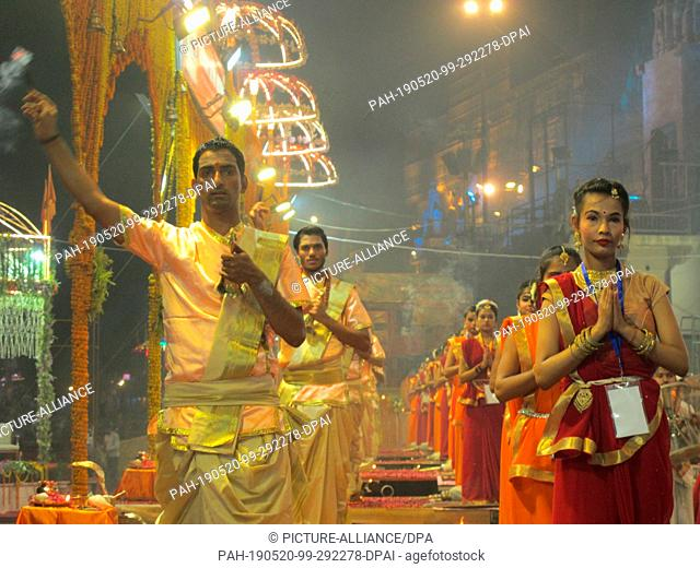 "26 April 2019, India, Varanasi: Young priests perform a ritual known as """"Aarti"""" or prayers on the banks of the Hindu holy river the Ganges"