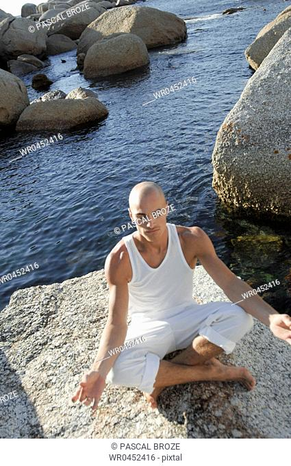 High angle view of a mid adult man meditating on a rock