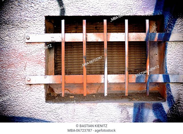 Close-up of a brightly painted cellar hole with rusted iron bars
