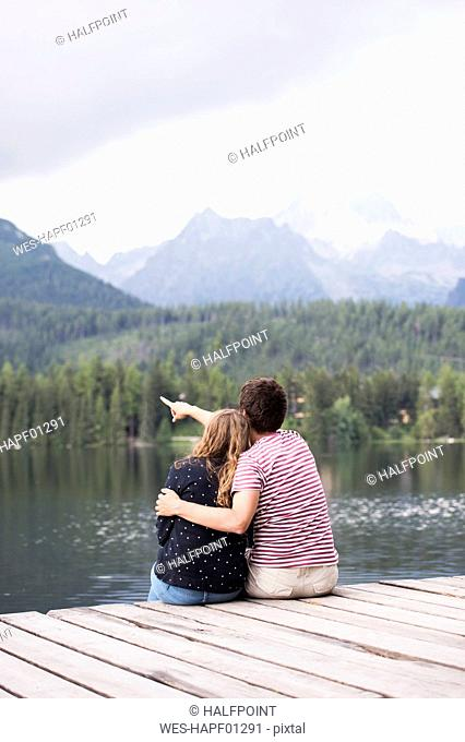 Back view of young couple sitting on a jetty at lake