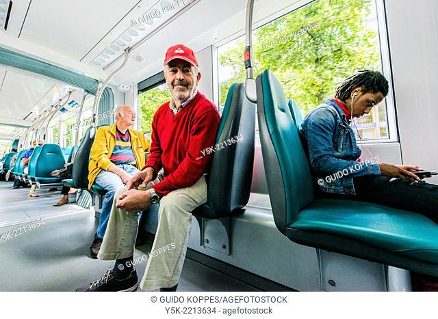 Rotterdam, Netherlands. Man wearing a red had and sweater, while traveling the city by tram trolley