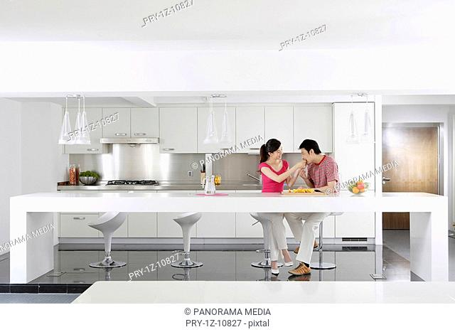 Young couple eating at kitchen