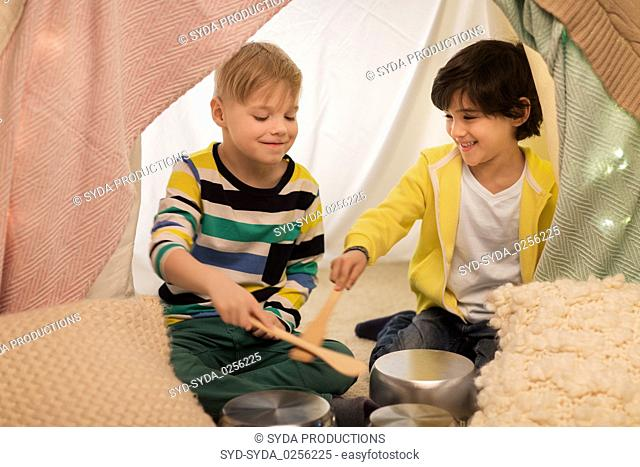 boys with pots playing music in kids tent at home