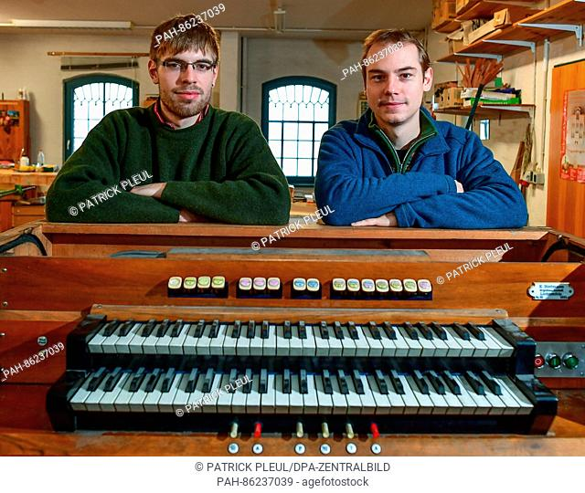 Konrad Scheffler (L), junior manager of the Organ Buidling business and the apprentice Richard Melzer stand behind an old organ console in their workshop in...